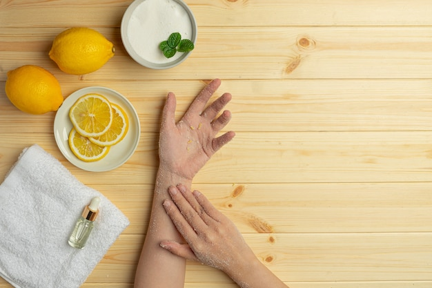 Young woman applying natural lemon scrub on hands against wooden table