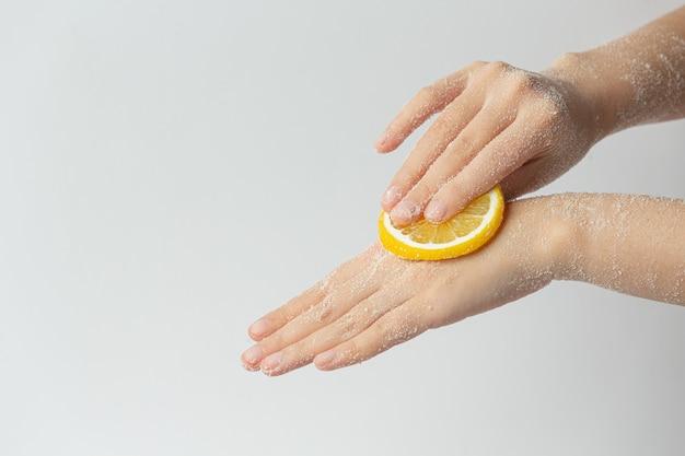 白い表面に対して手に天然レモンスクラブを適用する若い女性