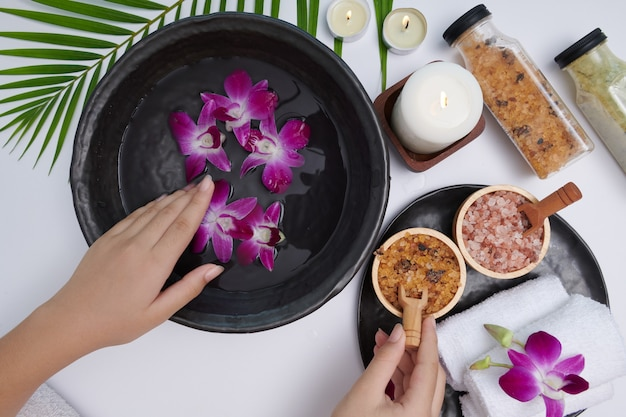 Young woman applying natural scrub on hands against white surface. spa treatment and product for female hand spa, massage, perfumed flowers water and candles, relaxation. flat lay. top view.