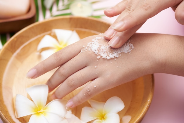 Young woman applying natural scrub on hands against white surface. spa treatment and product for female hand spa, massage, perfumed flowers water and candles, relaxation. flat lay. top view. Premium Photo