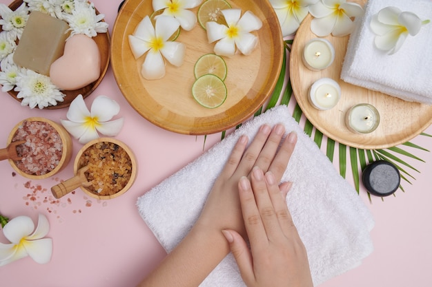 ピンクの表面に対して手に自然なスクラブを適用する若い女性。女性のハンドスパ、マッサージ、香りのよい花の水とキャンドル、リラクゼーションのためのスパトリートメントと製品。フラットレイ。上面図。