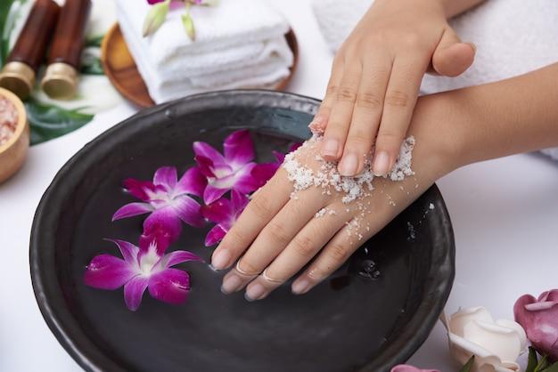 白い表面に対して手に自然なスクラブを適用する若い女性。女性のハンドスパ、マッサージ、香りのよい花の水とキャンドル、リラクゼーションのためのスパトリートメントと製品。フラットレイ。上面図。