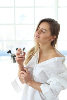 香水を適用する若い女性。
