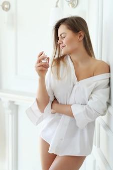 Молодая женщина, применяя духи.