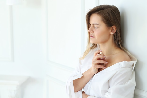 Young woman applying perfume.