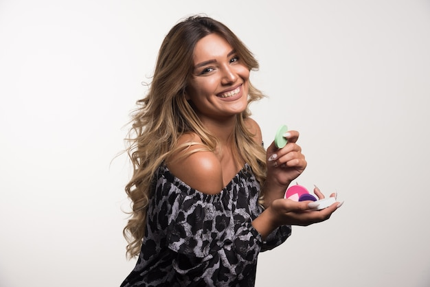 Young woman applying powder happily on white wall.