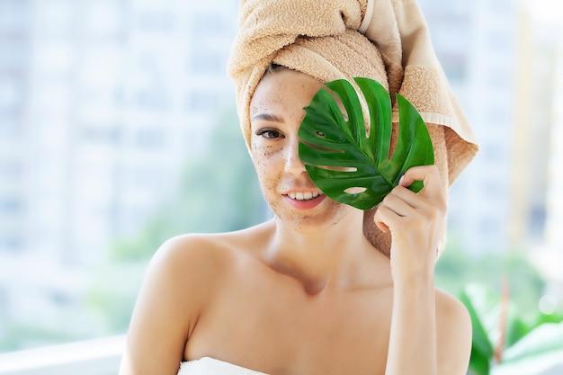 Young woman applying scrub on face in bathroom.
