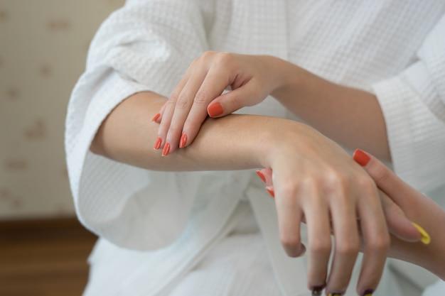 손에 손가락 흰색 보습 크림을 적용하는 젊은 여자.