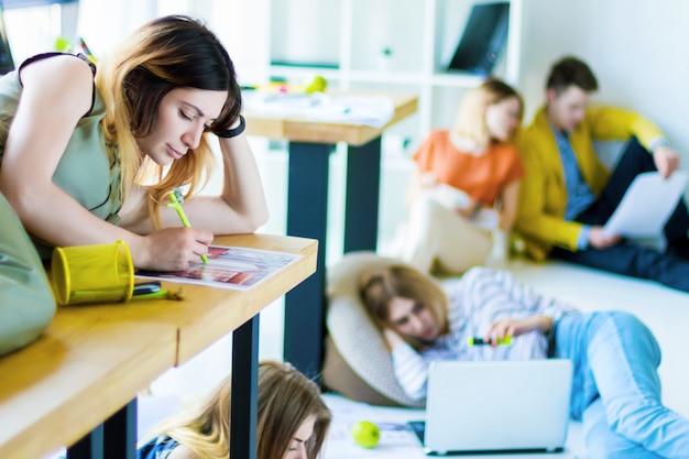 若い女性の建築家、軽いオフィスのデスクトップに横たわって働くインテリアデザイナー。背景に、創造的な労働者は、床に座って非公式の会合でデザインプロジェクトについて考えています。