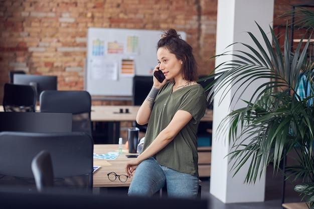 Молодая женщина-архитектор или дизайнер интерьера смотрит в сторону во время разговора по телефону, стоя в