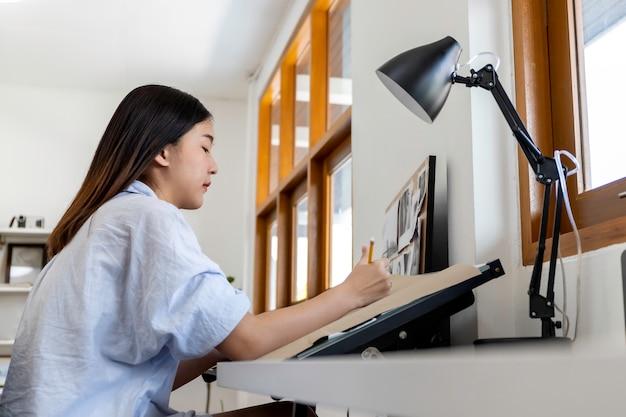 Молодая женщина архитектор работает из дома, зарисовка жилищного проекта.