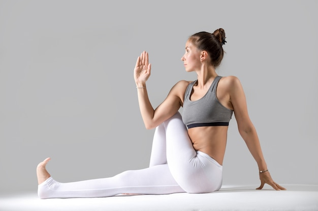 Young woman in ardha matsyendrasana pose, grey studio background