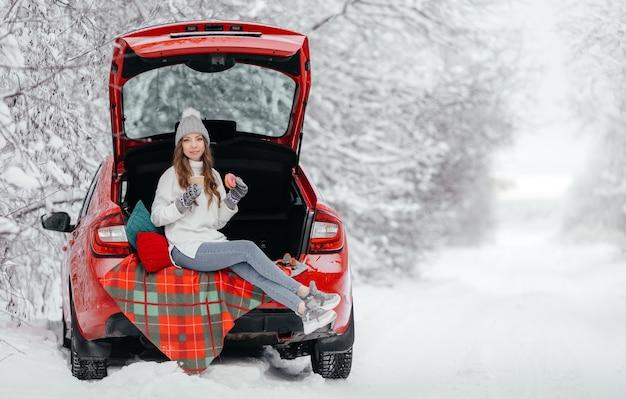 若い女性が冬の森の車に座ってコーヒーを飲む