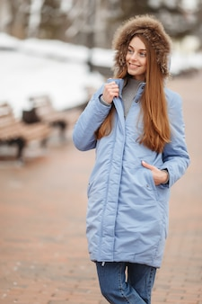 Young woman are walking in the winter park. winter park in the snow. clothing advertising photo concept.