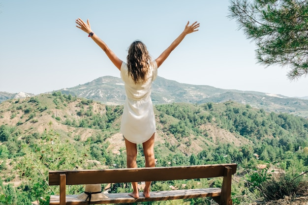Young woman arms raised up to sky, celebrating freedom. positive emotions feeling, peace of mind concept