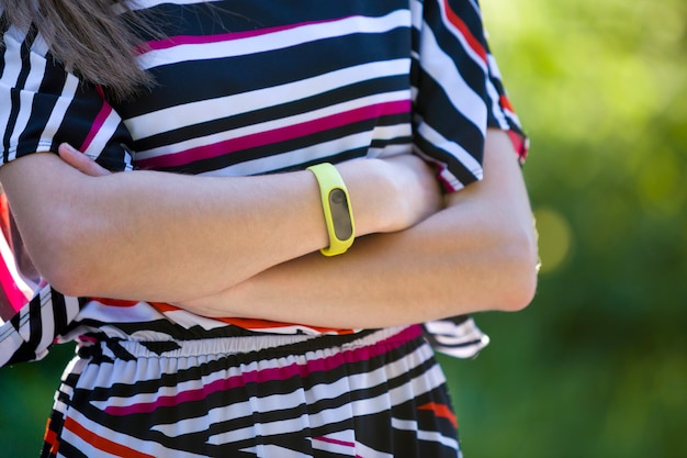 Young woman arms with fitness bracelet on outdoors blurred.