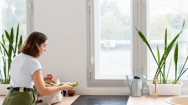 Young woman arranging organic vegetables in the kitchen