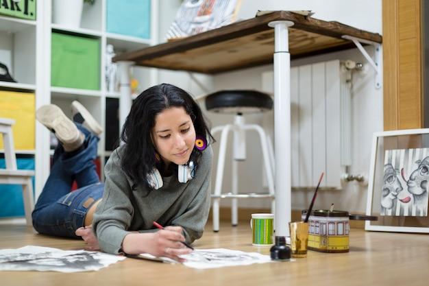 水彩絵の具で絵を描きながら、家で時間を楽しんでいる若い女性アーティスト。