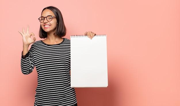 젊은 여성 아티스트가 행복하고 편안하고 만족감을 느끼고 괜찮은 제스처로 승인을 보여주는 미소