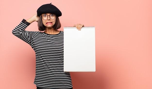 Молодая женщина-художник, чувствуя стресс, беспокойство, беспокойство или испуг, с руками на голове