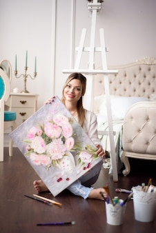 A young woman artist holds a picture on an easel at home. the painter paints oil paintings.