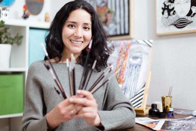 さまざまな種類のブラシを見せて笑っている彼女のスタジオの若い女性アーティスト。
