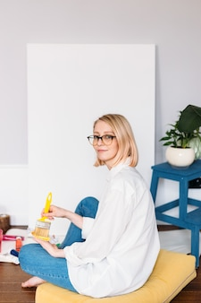 Young woman artist is painting at home in a creative studio setting