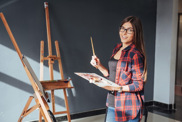 Young woman artist painting a picture
