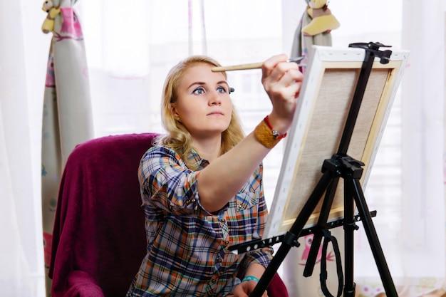 若い女性アーティストは、窓の向かいのイーゼルでインスピレーションを得てペイントします