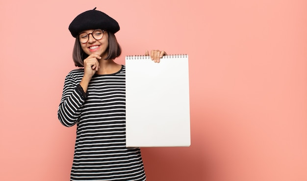 Молодая женщина-художник улыбается со счастливым, уверенным выражением лица, положив руку на подбородок, задается вопросом и смотрит в сторону