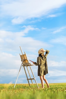 Young woman artist with easel outdoors on summer sunny evening