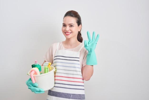 Молодая женщина как уборщица держит ведро, полное жидкости и показывает знак ок, изолированные на белом