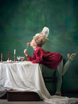 Young woman as marie antoinette on dark