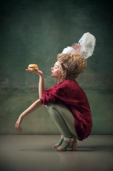 Молодая женщина в роли марии-антуанетты на темном фоне в стиле ретро, сравнение концепции эпох