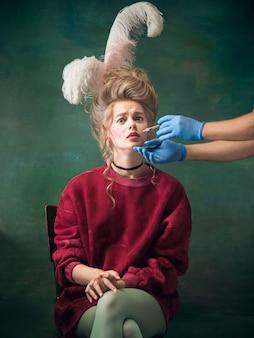 Молодая женщина в роли марии-антуанетты в темноте.