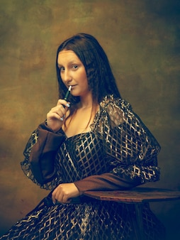 Young woman as mona lisa, la gioconda isolated on dark green