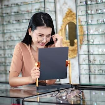 若い女性アジアは眼鏡店でメガネを選んでいます。