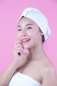 Молодая женщина азии с чистой свежей кожей касается собственного лица, выразительных выражений лица, косметологии и спа.