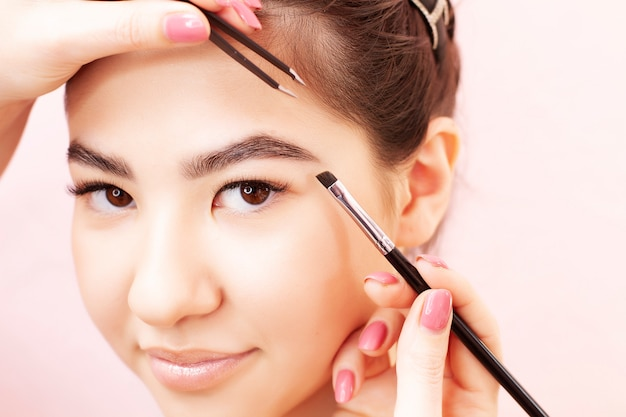 A young woman of asian appearance makes eyebrow correction on a pink.