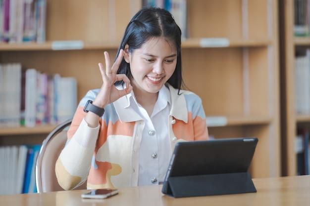 Covid-19 전염병 동안 교실이 제한된 동안 대학 도서관에서 디지털 태블릿이나 노트북을 사용하여 온라인으로 공부하고 책을 읽고 학생복을 입은 젊은 아시아 대학생