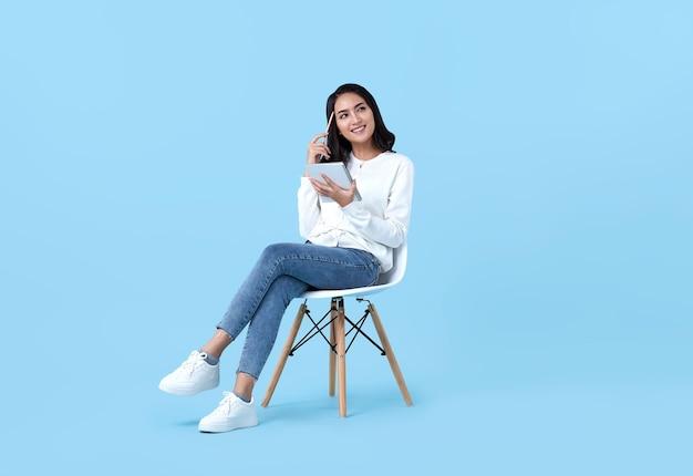 若い女性アジア人は幸せで、考えることに興味を持っています。白い椅子に座っている彼女のノートを保持している間、明るい青で隔離します。