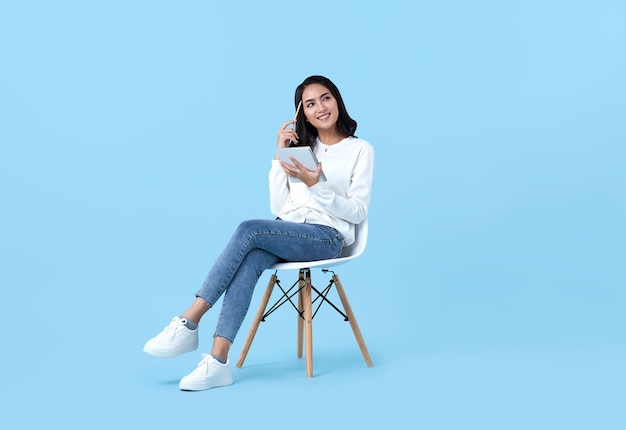 Young woman asian happy and interested in thinking.while her holding notebook sitting on white chair isolate on bright blue.