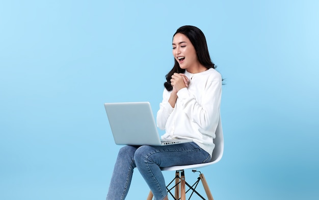 Young woman asian happy smiling in casual white cardigan with denim jeans.while her using laptop sitting on white chair isolate on bright blue space.