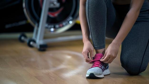 젊은 여자 아시아는 운동을 실행 한 후 피트니스 체육관에서 자신의 구두 끈을 할 아래로 무릎을 꿇