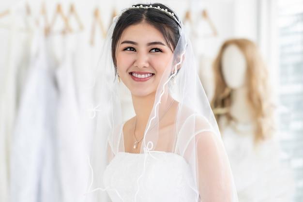 Молодая женщина азии улыбается и пытается на свадебное платье в магазине.