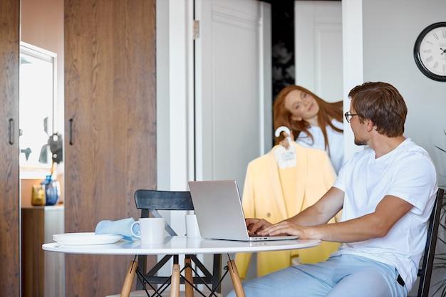 Молодая женщина спрашивает мнение работающего мужа
