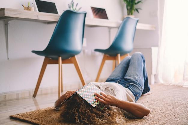 バックグラウンドでワークステーションコンピュータと自宅のカーペットの上で眠っている若い女性。女性は目を覆っている本を持って居間の床で寝る