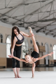 Young woman assisting ballerina girl in dance class