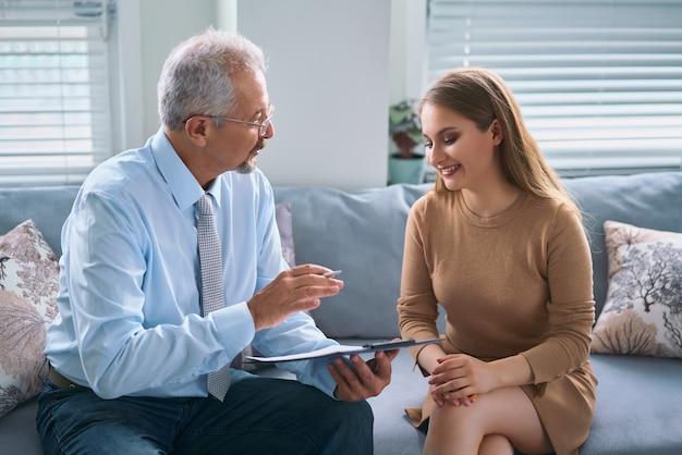 心理療法士と相談している若い女性。彼女の患者とのセッションを持っている心理学者
