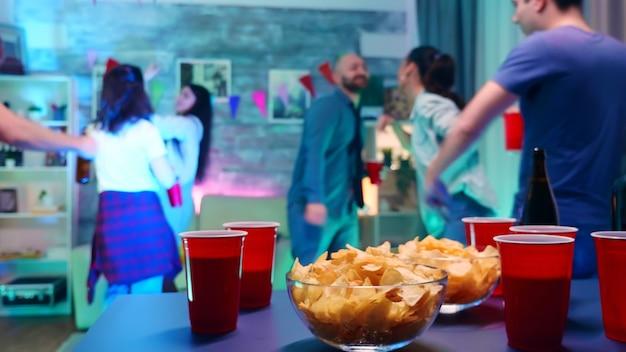 테이블에서 칩을 가져오는 네온 불빛과 맥주 한 잔을 들고 파티에 참석한 젊은 여성. 야생 대학 파티에서 배경에서 춤을 추는 젊은이들